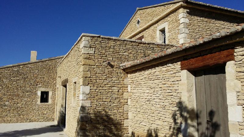 Doublage en pierre à bâtir de pays avec chaine d'angle en pierre de récupération par Luberon Batiment, entreprise spécialisée en construction en pierre.