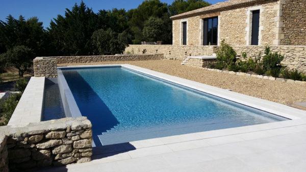 Création d'une piscine à débordement en béton armé avec volet roulant intégré par Luberon Batiment.