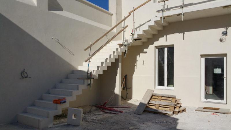 Réalisation d'un escalier en béton blanc architectonique coffré et coulé sur place pour un cabinet dentaire à Chateaurenard par Luberon Batiment.